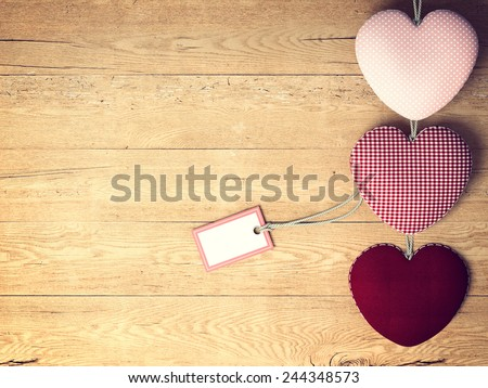 Valentines Day background with patterned textile hearts on old wooden - stock photo