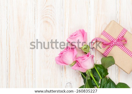 Valentines day background with pink roses over wooden table and gift box. Top view with copy space  - stock photo