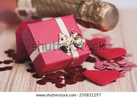 Valentines day: bottle of vine, red hearts and small present - stock photo
