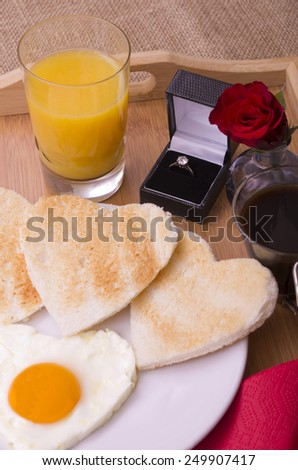 Valentines Day Breakfast on a Tray With Diamond Ring Romantic valentines day breakfast of a heart shaped egg,  heart shaped toast, a red rose orange juice and black coffee with a diamond ring. - stock photo