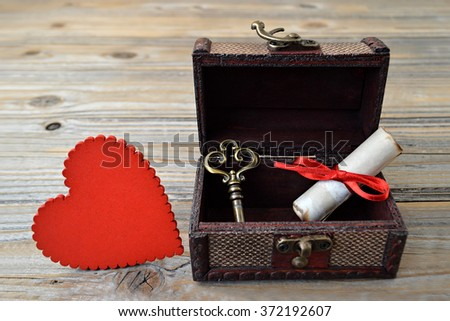 Valentines Day card: Heart, love letter and key in wooden treasure chest - stock photo