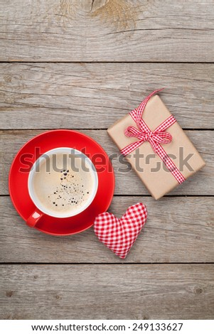 Valentines day gift box, toy heart and coffee cup over wooden table with copy space - stock photo