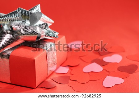 Valentines Day gift in box and small hearts on red background - stock photo