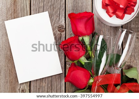 Valentines day greeting card, gift box and red roses on wooden table. Top view with copy space - stock photo