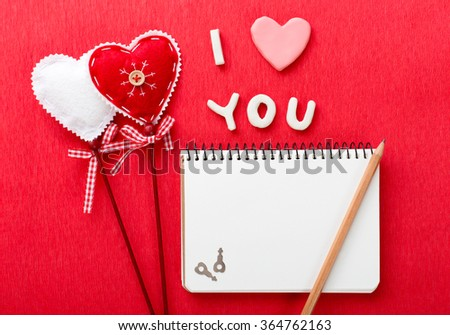 Valentines day hearts and pencil, keys, notebook, text i love you over red background. Top view with copy space - stock photo