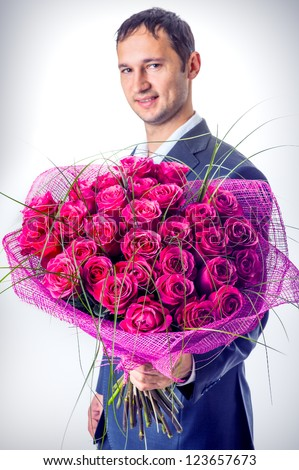 Valentines day. Man holding big bouquet of flowers. Proposal scene - stock photo