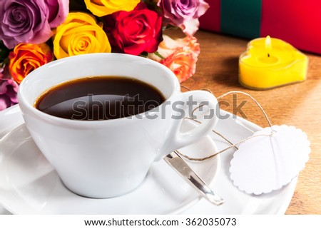 Valentines Day or anniversary breakfast with a cup of freshly brewed black coffee with a blank gift tag on the saucer alongside a bouquet of colorful roses and heart shaped burning candle - stock photo