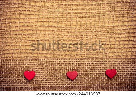 Valentines day or wedding concept. Red wooden decorative hearts bagging ribbon on abstract cloth burlap background with copy space. Vintage aged tone - stock photo