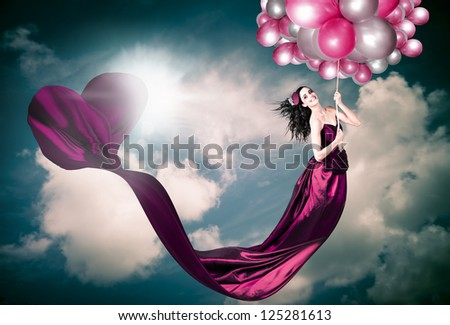 Valentines Day Photograph Of A Smiling Beautiful Retro Girl Hanging From The Sky With Draping Heart Shaped Dress In A Depiction Of Fashion Love - stock photo