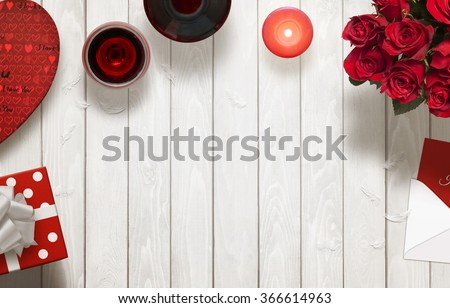Valentines day romantic background with gifts, glasses of wine, candle, roses, envelope on wooden table. - stock photo