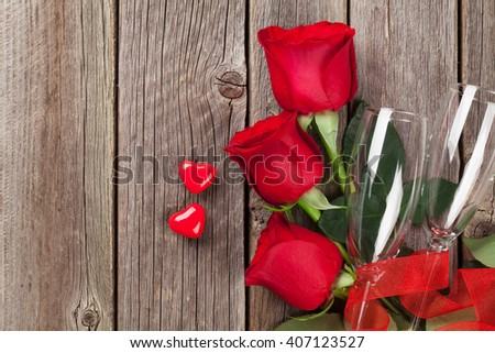 Valentines day roses bouquet, candy hearts and champagne glasses on wooden table. Top view with copy space - stock photo