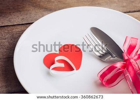 Valentines day table setting with plate, knife, fork, red ribbon and hearts on wooden table, Valentines day background - stock photo