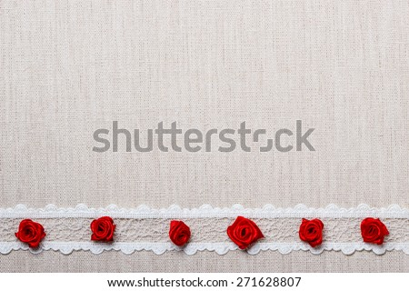Valentines day, wedding, invitation or greeting card. Red decorative silk rose flowers, lace ribbon on pastel linen cloth background. Border frame. - stock photo