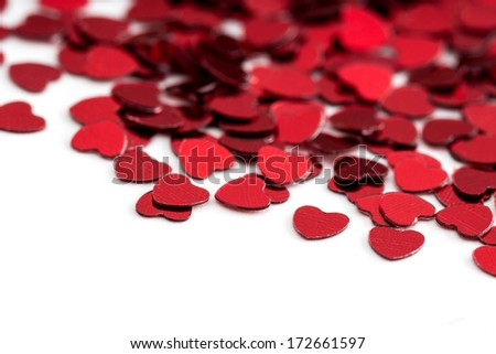 Valentines decoration of red confetti hearts against white background with bokeh - stock photo