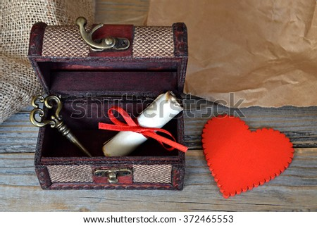 Valentines heart, love letter and key in old wooden treasure chest - stock photo