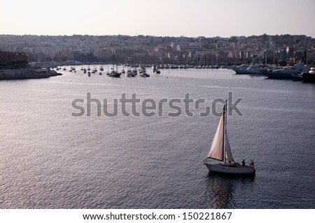 Valletta in violet sunset hours. View to Valletta in Malta. Malta in night time with boats in the sea, nice reflections on a water. Malta. Sunset hours with nice mist view to the city. Malta island - stock photo