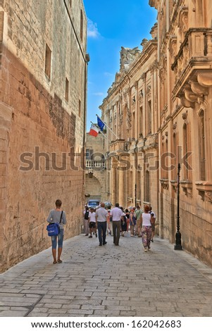 Valletta, Malta - SEPTEMBER 11, 2013: Tourists walking up in the old streets of Malta. - stock photo