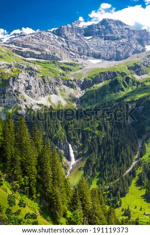 Valley with the Waterfall surrounded by mountains near Klausen Pass road in Swiss Alps, Switzerland - stock photo
