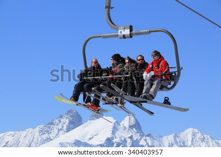 VALLOIRE, FRANCE - MARCH 23, 2015: Skiers go up the lift in Galibier-Thabor station in France. The station is located in Valmeinier and Valloire and has 150km of ski runs. - stock photo