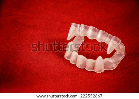 Vampire Costume Fangs on Red. Classic Halloween costume vampire teeth with fangs on red. - stock photo
