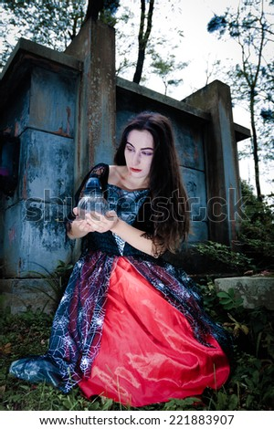 Vampire gilr portrait sitting on cemetery with icon lamp - stock photo