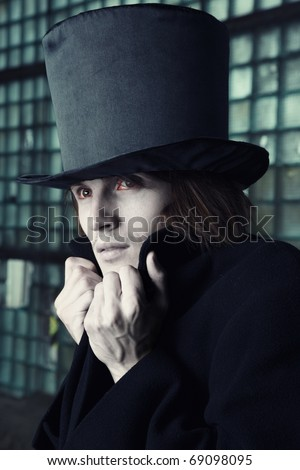 Vampire man with bloody eyes in the black coat and top hat indoors. Natural makeup colors - stock photo
