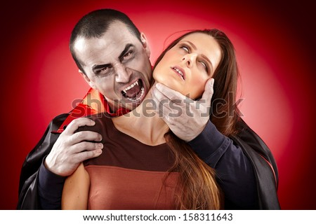 Vampire preparing to bite a beautiful woman's neck - stock photo