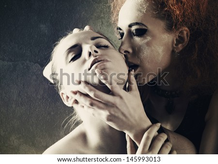Vampire's kiss. Fantasy female portrait against dark grungy backgrounds - stock photo