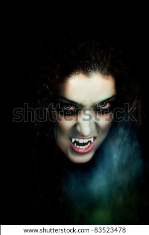 Vampire with pale face, fangs, flaky skin and scary eyes - stock photo