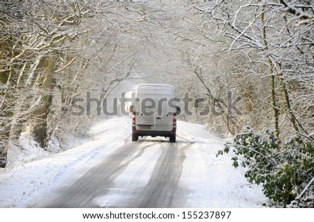 Van driving on winter snow covered country lane through woodland trees - stock photo