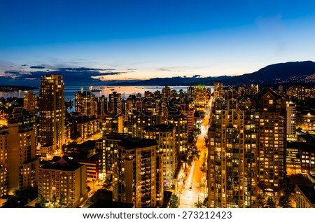 Vancouver at night. Sparkling aerial view of downtown and bay. Illuminated buildings and deep blue sky. - stock photo