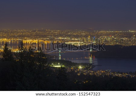 Vancouver BC Canada Cityscape with Stanley Park and Lions Gate Bridge Over Burrard Inlet at Evening Blue Hour - stock photo