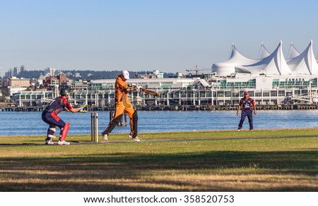 VANCOUVER, BC, CANADA - JULY 19, 2015: Young men play cricket on a field in front of Canada Place.  - stock photo