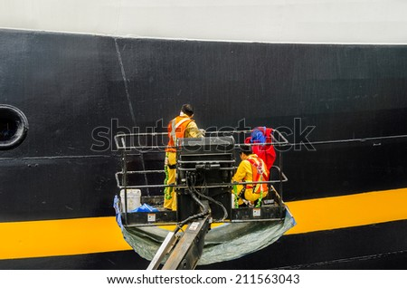 Vancouver, BC, Canada - June 23, 2014: Workers Painting the Starboard of a Cruise Ship Moored to Canada Place Pier. Canada Place is the main Cruise Terminal where most cruises to Alaska originate. - stock photo