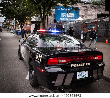 VANCOUVER, BC, CANADA - MAY 11, 2016: VPD cruiser on Vancouver's Downtown Eastside with officers in the background dealing with an issue - stock photo