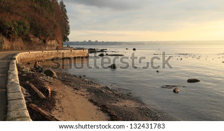 VANCOUVER, BRITISH COLUMBIA - MAR 10: A couple watches the sunset at Ferguson Point on March 10, 2013 in Vancouver. - stock photo