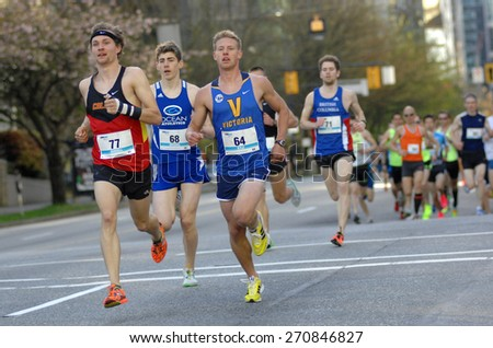 VANCOUVER, CANADA - APRIL 19, 2015: Thousands of participants run the streets during annual Vancouver Sun Run in Vancouver, Canada, on April 19, 2015. - stock photo
