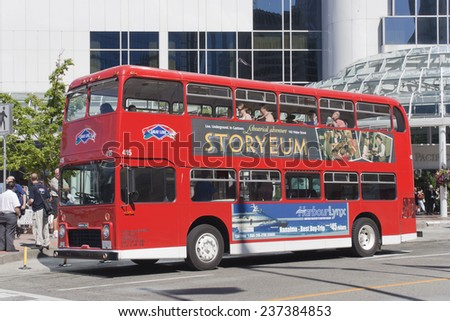 VANCOUVER, CANADA - AUGUST 6, 2005: Red double-decker bus standing on bus stop in Vancouver, Canada. Tourists enjoy a Vancouver Sightseeing Tour. In the background the Pan Pacific Hotel. - stock photo