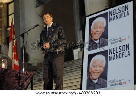 VANCOUVER, CANADA - DECEMBER 6, 2013: Major of Vancouver Gregor Robertson (L) attends a candlelight vigil for first black president of South Africa Nelson Mandela in Vancouver, Canada, Dec.6, 2013.  - stock photo