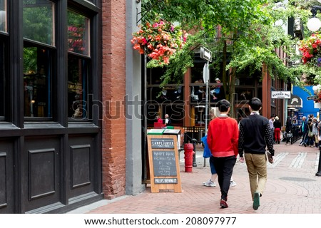 VANCOUVER-JUN 27, 2014:Vancouver's trendy Gastown district, an historic neighborhood known for its restaurants, nightlife, art galleries and upscale shops. Popular with locals and tourists. - stock photo