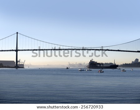 Vancouver, Lions Gate Bridge with fishing boats and trans-ocean transporter, British Columbia, Canada - stock photo