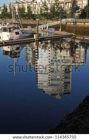 Vancouver Reflections, Yaletown. Early morning reflection of a False Creek marina and Yaletown condominiums in downtown Vancouver. A seawall walk rings the harbor. British Columbia, Canada. - stock photo