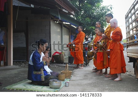 VANG VIENG, LAOS - SEPTEMBER 7: Unidentified monks beg for food on street on September 7, 2011, in Vang Vieng, Laos. About 60% of the population of Laos practice Theravada Buddhism. - stock photo