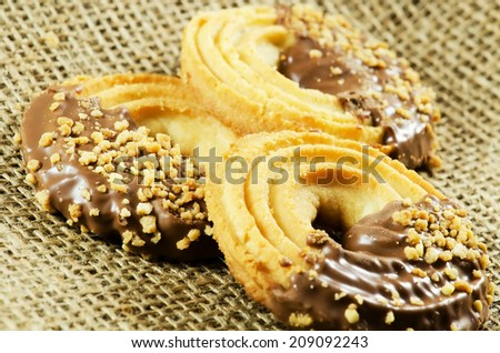 Vanilla biscuits with chocolate and hazelnut on a jute texture. - stock photo