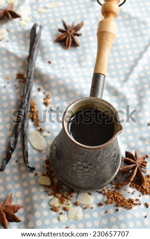 Vanilla coffee in traditional cezve with a vanilla pod and anise star - stock photo
