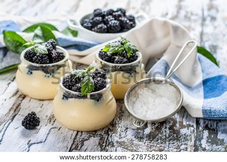 vanilla cream with blackberries and caster sugar - stock photo