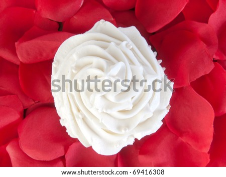 vanilla cupcake surrounded by rose petals - stock photo