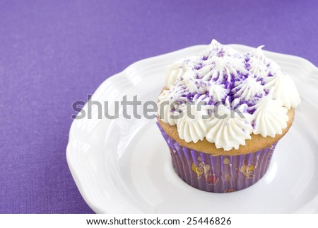 Vanilla cupcake with purple sugar sprinkles and purple decorative paper on a plate with solid purple background, corner with copy space - stock photo