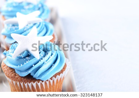 Vanilla cupcakes with blue frosting and a big star, christmas birthday party  - stock photo