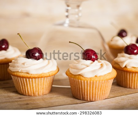 vanilla cupcakes with butter cream frosting and a cherry on top - stock photo